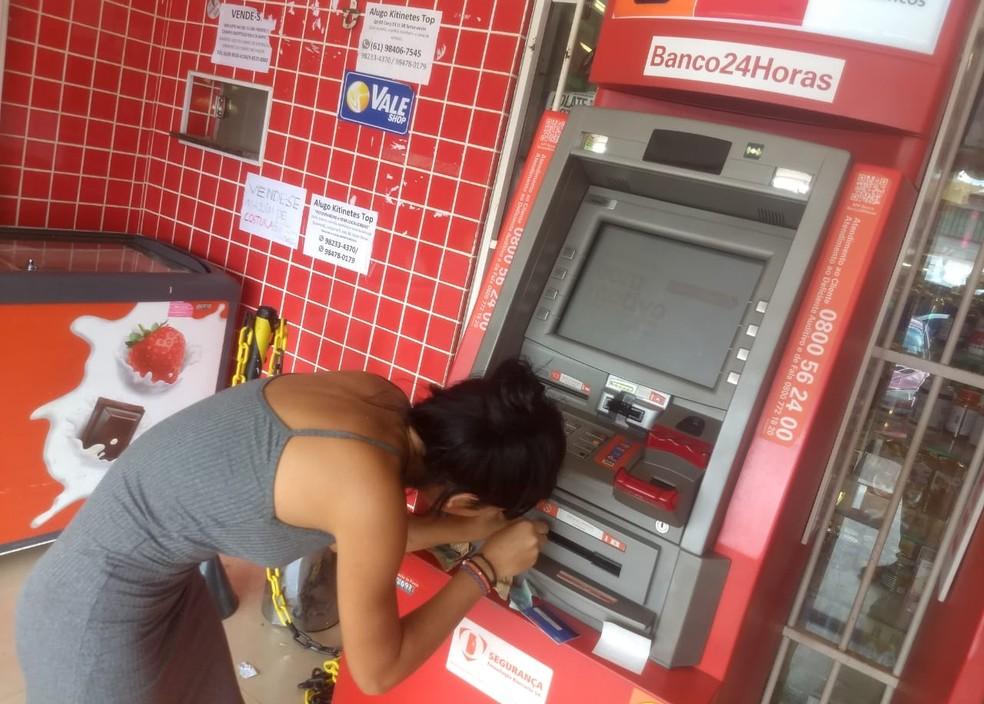 Estudante Naely Rodrigues tenta tirar notas emperradas em caixa eletrônico após saque no DF — Foto: Arquivo pessoal