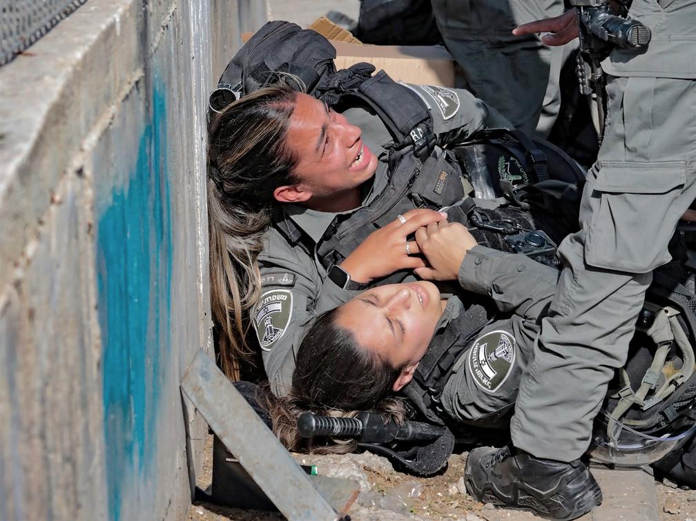 Policiais israelenses reagem após serem atropeladas em ataque com carro a um posto de controle no bairro de Sheikh Jarrah, na região anexada de Jerusalém oriental — Foto: Yossi Zamir/AFP