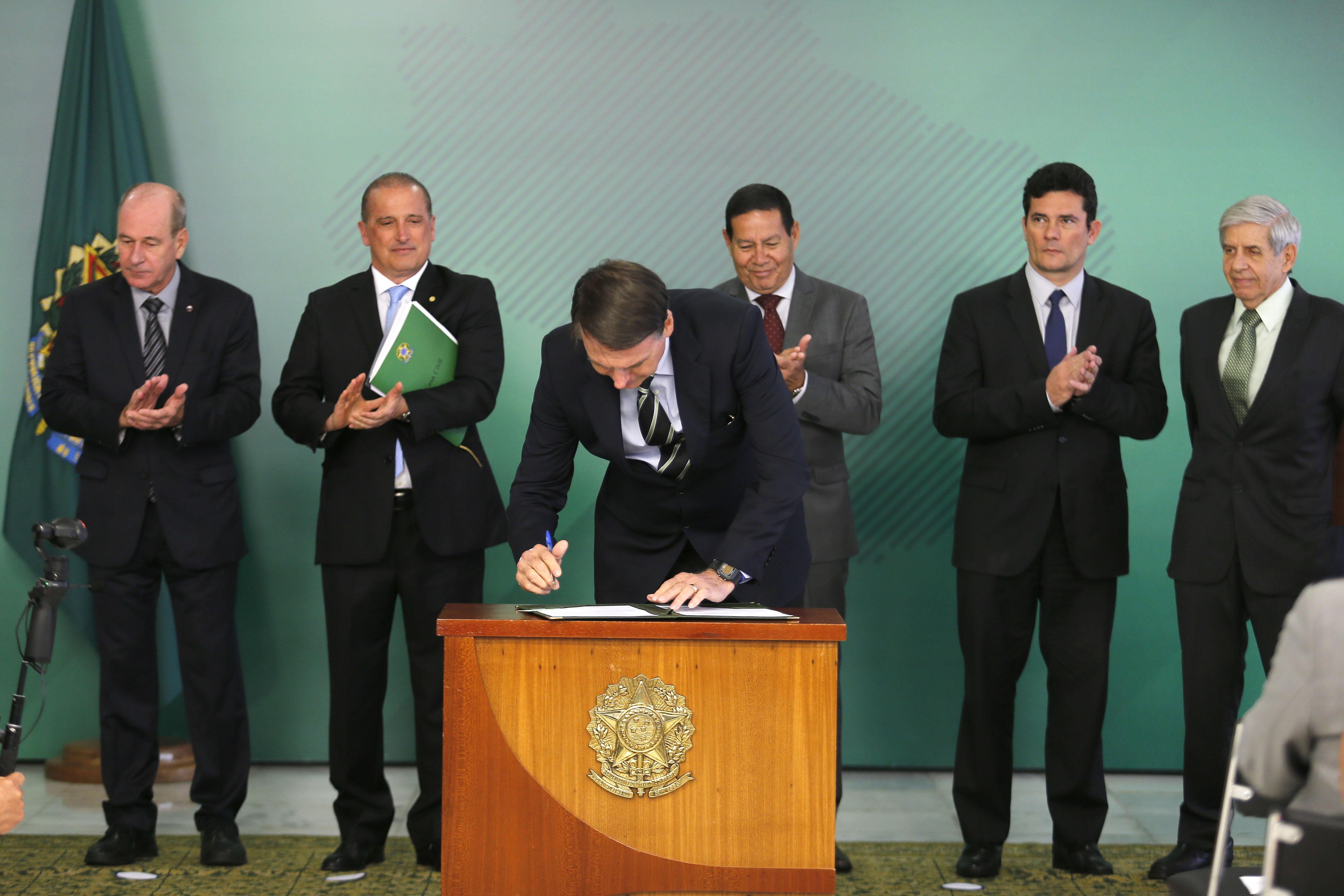 O presidente Jair Bolsonaro assina o decreto de (Foto: Agência O Globo)