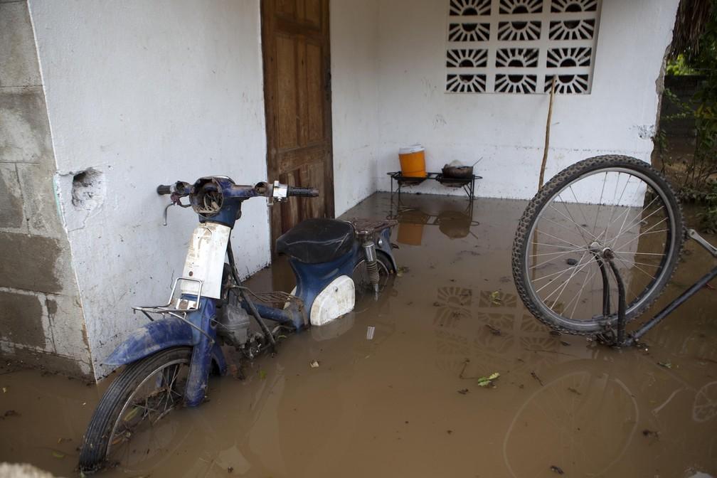 Uma moto e uma bicicleta são vistas parcialmente submersas em região alagada após passagem do furacão Irma, em Fort-Liberte, no Haiti (Foto: Dieu Nalio Chery/AP)