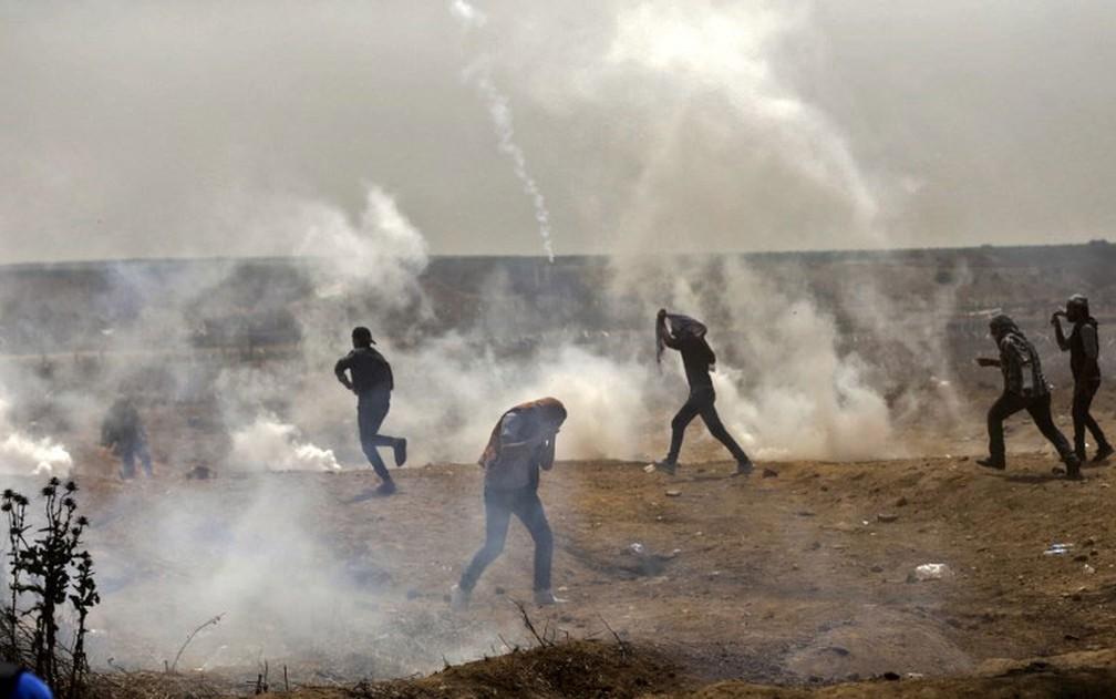 Palestinos se deslocam em meio ao gás lacrimogêneo durante confronto com as forças de segurança israelenses nesta sexta-feira (13)  (Foto: Mahmud Hams / AFP)