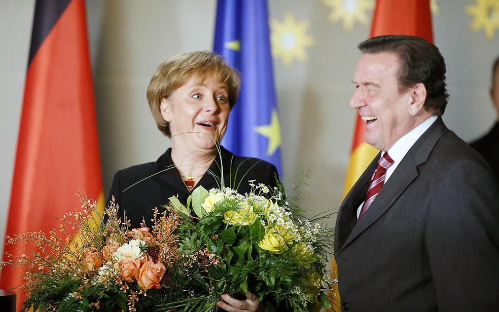O ex-primeiro-ministro alemão Gerhard Schroeder transmite o cargo à recém-eleita premiê Angela Merkel, em foto de 22 de novembro de 2005 — Foto: Michael Hanschke/DPA via AFP