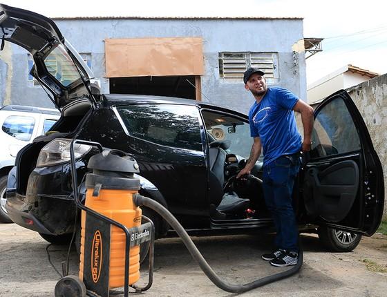 Macarrão limpa carros em lava a jato improvisado. Recorre a publicidade em redes sociais e a preços menores contra concorrentes formais (Foto: EDILSON DANTAS/AGÊNCIA O GLOBO)