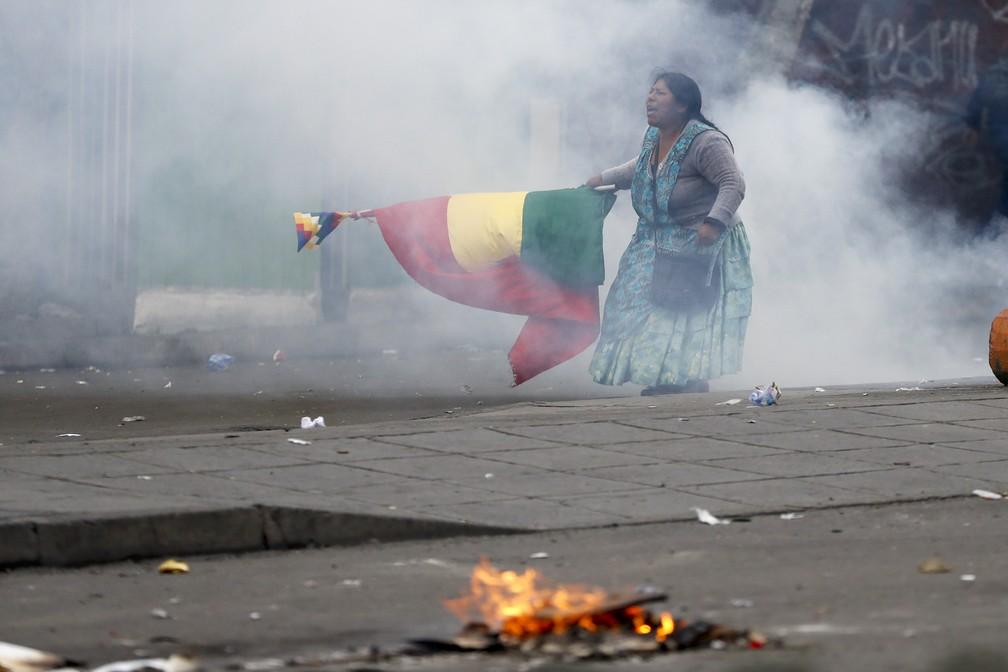 Manifestante com bandeira da Bolívia e Wiphala protesta em La Paz nesta quarta-feira (13) em meio a névoa de gás lacrimogêneo — Foto: Natacha Pisarenko/AP Photo
