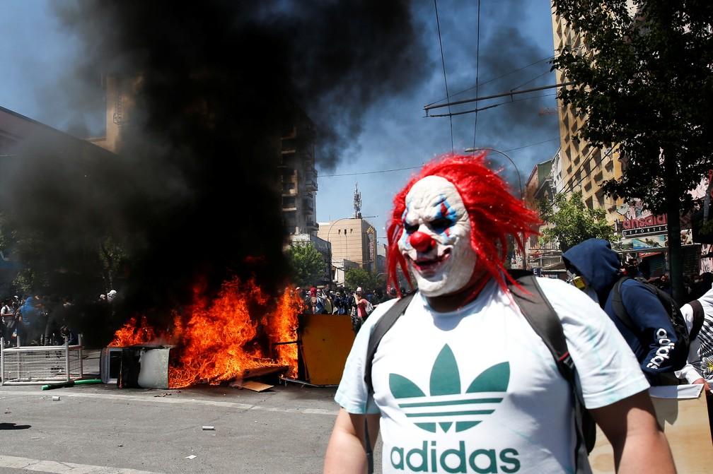 Manifestante vestido de palhaço em frente a barricada montada em Valparaíso, no Chile, nesta quinta-feira (24) — Foto: Rodrigo Garrido/Reuters