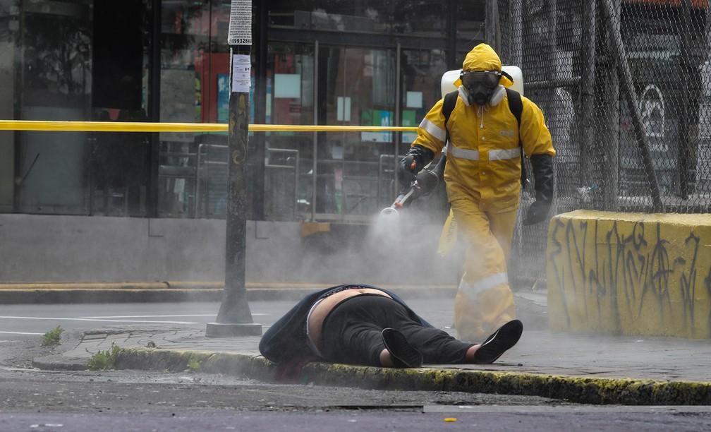 Funcionário do departamento forense da cidade de Quito, capital do Equador, aplica desinfetante no corpo de uma mulher que morreu na rua em 14 de maio de 2020 — Foto: Dolores Ochoa/AP