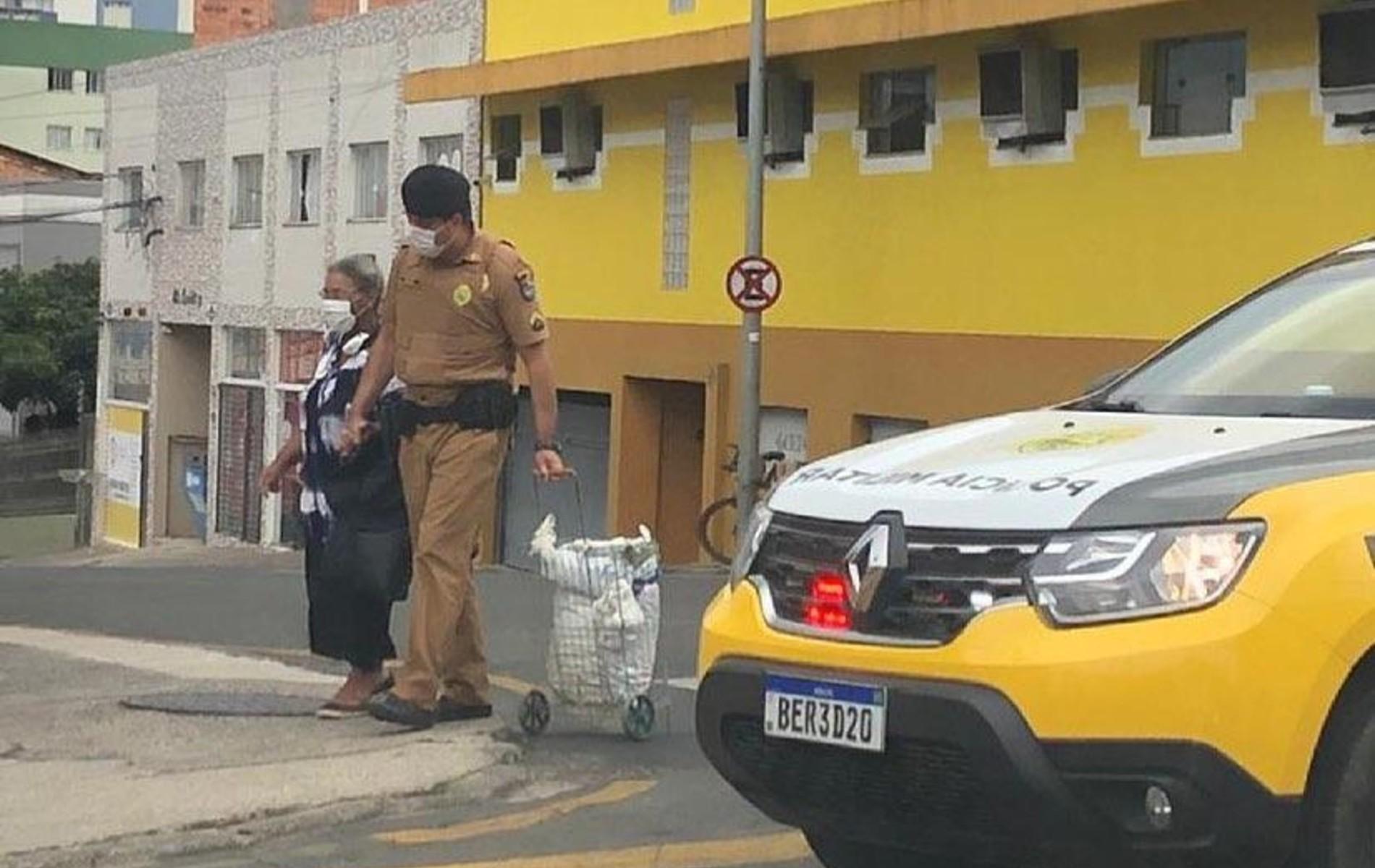 Policial desce de carro da PM e ajuda idosa a chegar em agência bancária, em Ponta Grossa; VÍDEO