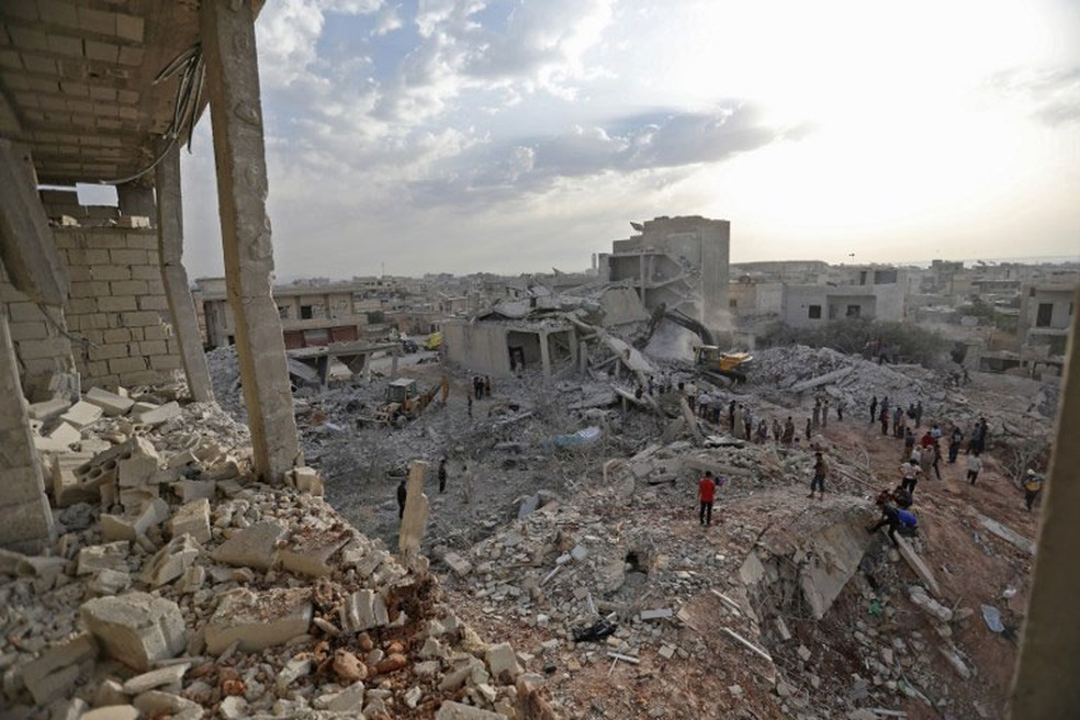 Sírios caminham sobre destroços em Zardana, em Idlib, nesta sexta-feira (8)  (Foto: Omar Haj Kadour / AFP)
