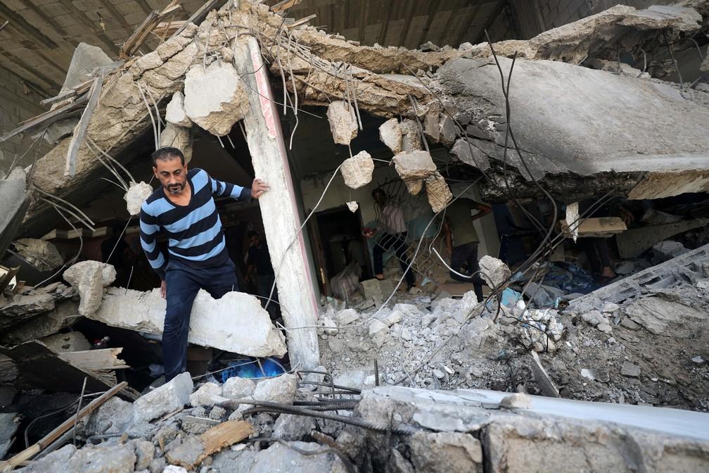 Um palestino caminha pelas ruínas após os ataques aéreos israelenses na Cidade de Gaza, nesta segunda (17)  — Foto: Mohammed Salem/Reuters