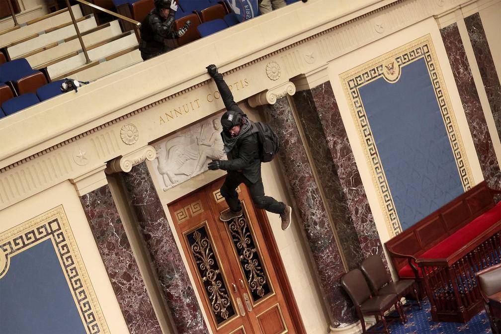 Apoiador de Trump de pendura da beira da galeria no plenário do Senado dos EUA, após invasão do Capitólio — Foto: Win McNamee/Getty Images/AFP