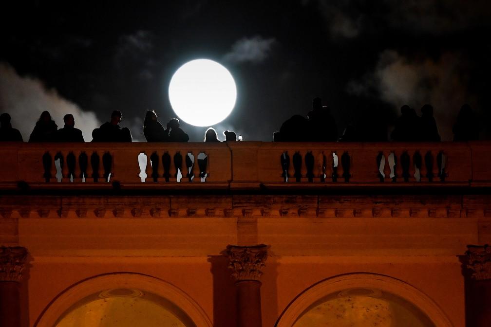 Pesooas observam a Superlua em Roma, na Itália (Foto: Alberto Pizzoli/AFP)