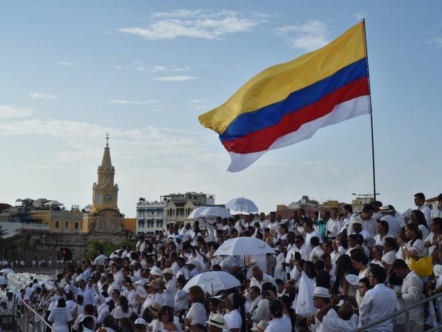 Vestidos de branco, alguns dos 2.500 espectadores esperam o início da cerimônia de assinatura do acordo para o conflito armado na Colômbia nesta segunda-feira (26) em Cartagena (Foto: LUIS ACOSTA / AFP)