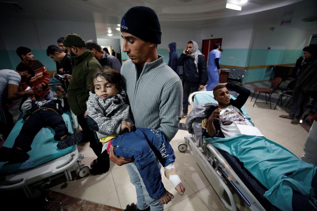 Homem carrega criança ferida por bombardeio israelense contra a Faixa de Gaza nesta sexta-feira (8) (Foto: Mohammed Salem/ Reuters)