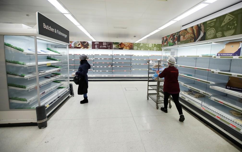 18 de março - Uma funcionária passa por um cliente próximo a prateleiras vazias em uma loja da Sainsbury em Harpenden, no Reino Unido, durante a epidemia do novo coronavírus (COVID-19) — Foto: Peter Cziborra/Reuters