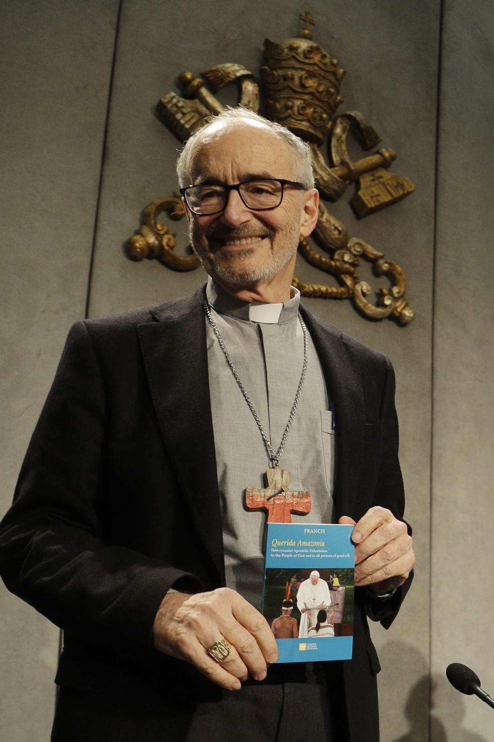 O cardeal Michael Czerny segura uma cópia da exortação apostólica pós-sínodo da Amazônia em uma coletiva de imprensa no Vaticano nesta quarta (12). — Foto: Gregorio Borgia/AP