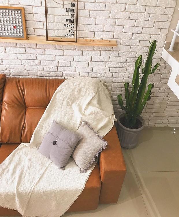 Paula Faria, do @moradadois, escolheu um sofá caramelo para acompanhar a parede de tijolinho pintada de branco - o conjunto de completa com o porcelanato cinza do piso e o pínus da canaleta dos quadros (Foto: Instagram/Reprodução)