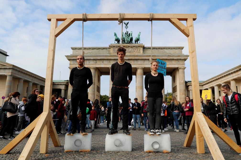Greve pelo Clima: Na Alemanha, ativistas sobem em blocos de gelo sob forca improvisada em frente ao portão de Brandemburgo, em Berlim, Alemanha, para alertar sobre os riscos do aquecimento global — Foto: Fabrizio Bensch/Reuters