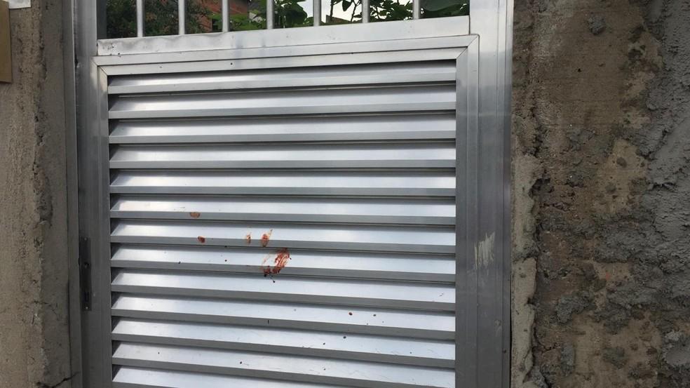 Porta da casa onde ocorreu série de assassinatos ficou com mancha de sangue  — Foto: G1 Santos