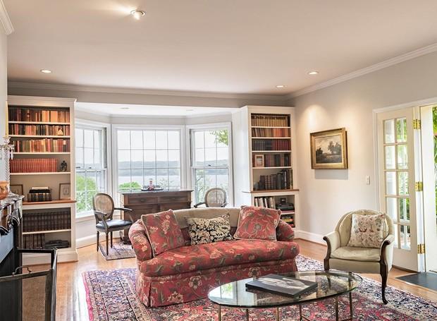 O escritório conta com uma pequena biblioteca e é decorado por móveis antigos e um tapete persa (Foto: Ellis Sotheby's International Realty/ Reprodução)