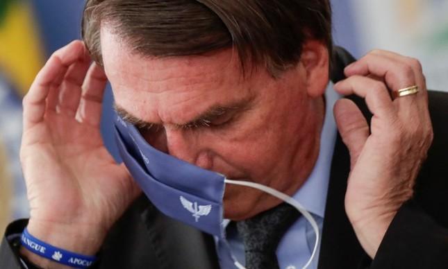 Presidente do Brasil, Jair Bolsonaro, tenta colocar a máscara durante cerimônia para anunciar investimentos para o Programa Águas Brasileiras, em Brasília