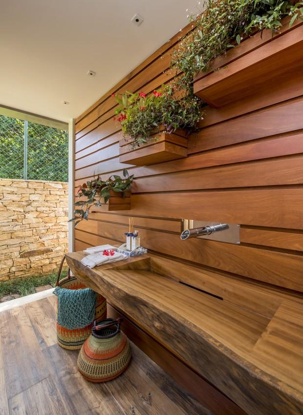 Aberta para o jardim, a bancada de madeira de demolição tem acesso fácil  (Foto: Marcio Irala/Divulgação)