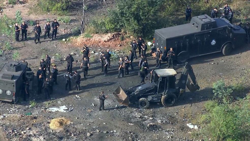 Blindado e retroescavadeira da polícia chegam a área de lixão no Salgueiro, em São Gonçalo — Foto: Reprodução/TV Globo