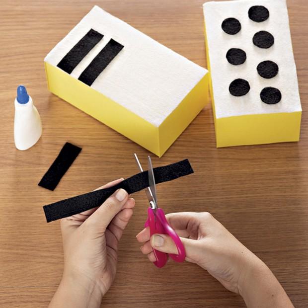 4. Corte tiras (2 cm x 7 cm) do feltro preto para montar as teclas. Faça, então, bolinhas (2 cm de diâmetro) para os botões. Cole-os nas caixas. (Foto: Bruno Marçal / Editora Globo)