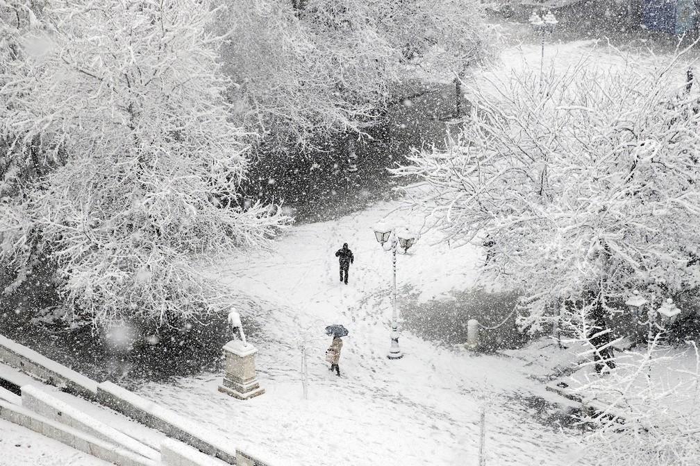 Pessoas caminham pela Praça Syntagma, em Atenas, coberta de neve durante forte nevasca — Foto: Alkis Konstantinidis/Reuters