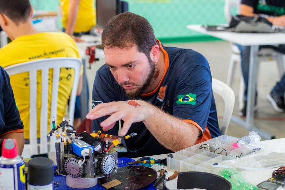 Membro da equipe Warthog Robotics com um dos robôs da categoria pequeno porte — Foto: Henrique Megid/Warthog Robotics/Divulgação