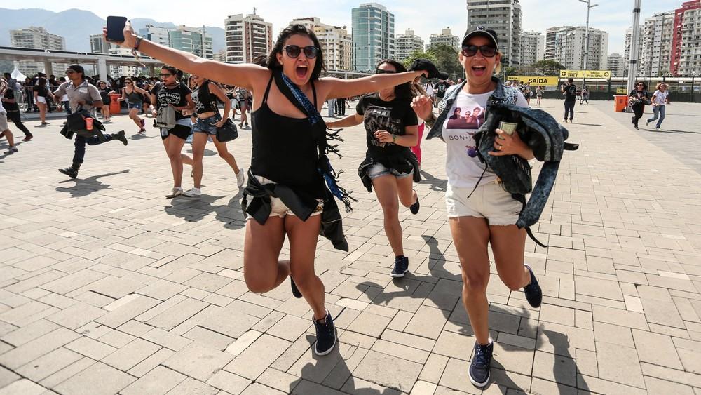 Fãs correm para aproveitar o início do quinto dia de festival após a abertura dos portões do Rock in Rio 2017
