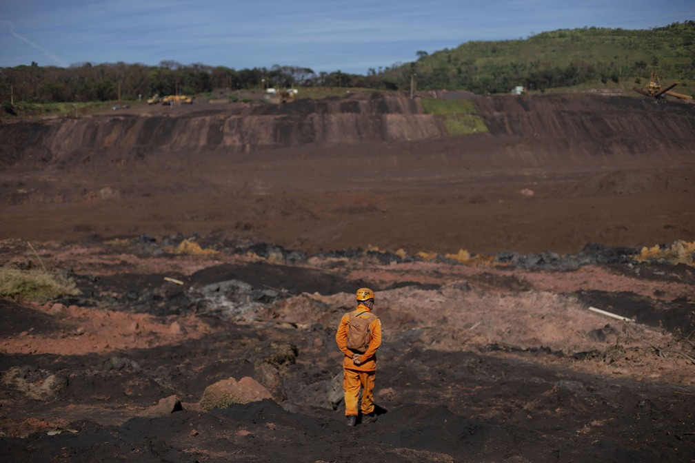 Bombeiro observa a lama que tomou conta do Córrego do Feijão em Brumadinho, dias após o colapso da barragem — Foto: Mauro Pimentel/AFP