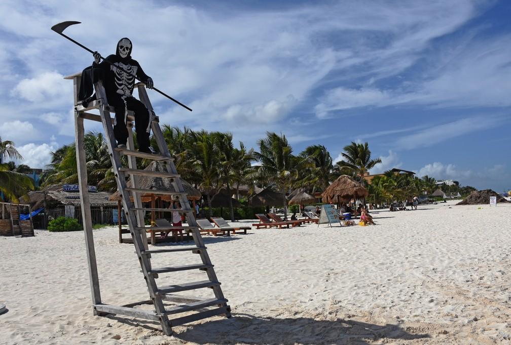 """Pessoa fantasiada da """"morte"""" passeia por praia em Puerto Morelos, no México, neste domingo (2), convidando as pessoas a voltarem para casa, porque as praias ainda estão fechadas para visitantes por causa da pandemia do novo coronavírus. O México é o terceiro país no mundo que mais perdeu vidas para a Covid-19, atrás de Estados Unidos e Brasil. — Foto: Elizabeth Ruiz/AFP"""
