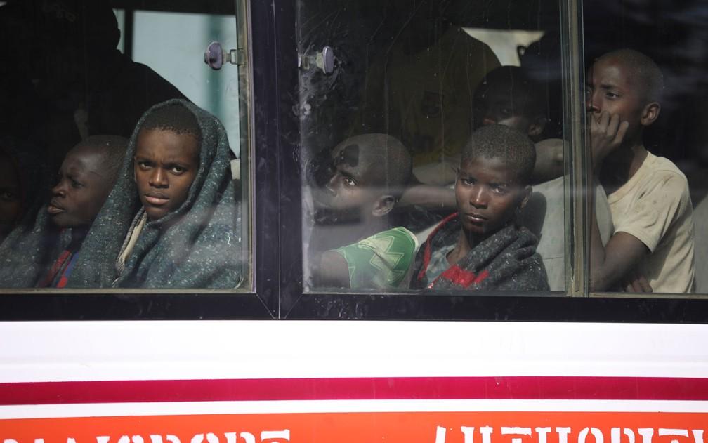 Meninos que haviam sido sequestrados pelo Boko Haram são vistos através da janela de ônibus ao serem levados até a sede do governo do estado de Katsina, na Nigéria, após terem sido libertados, na sexta-feira (18) — Foto: Kola Sulaimon/AFP