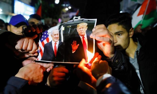 Manifestantes queimam foto de Trump e Netanyahu durante protesto em Ramallah, na Cisjordânia