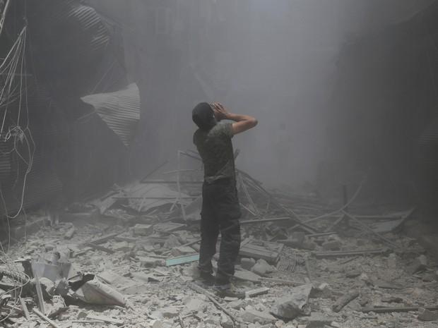 Sírio faz buscas em local após ataque aéreo das forças do governo no domingo (5) em bairro controlado pelos rebeldes em Aleppo (Foto: Baraa Al-Halabi/AFP)