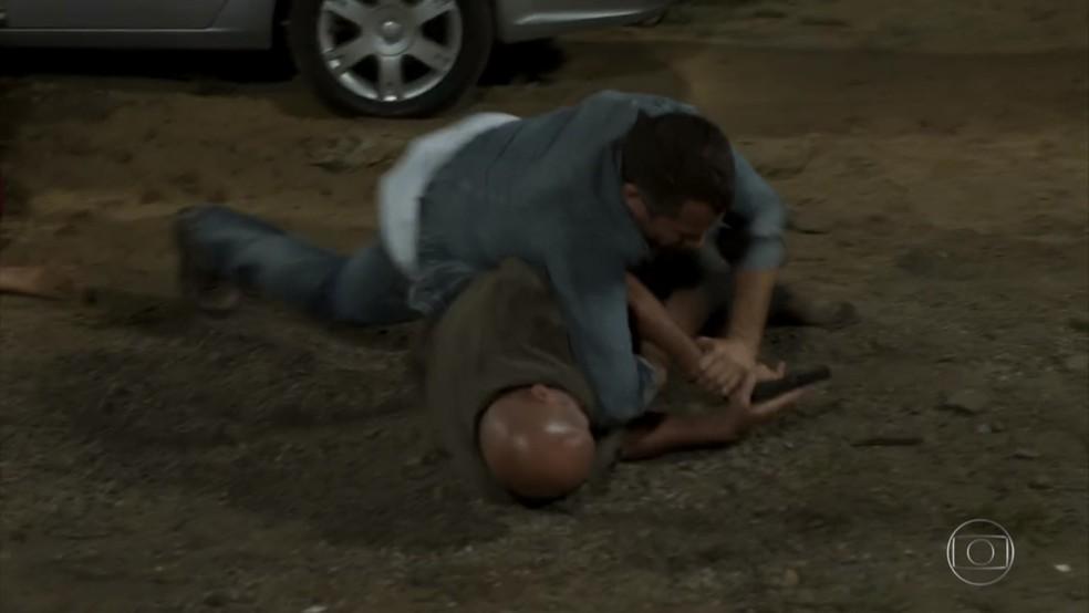 Apolo (Malvino Salvador) tenta desarmar Genésio (Cláudio Galvan) - 'Haja Coração' — Foto: Globo