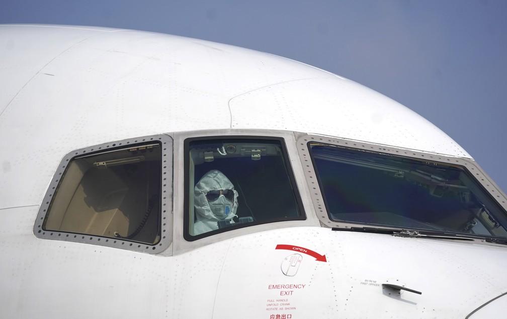 Coronavírus - piloto usa traje de proteção dentro de avião no Aeroporto Internacional de Wuhan, na China — Foto: Cheng Min/Xinhua via AP