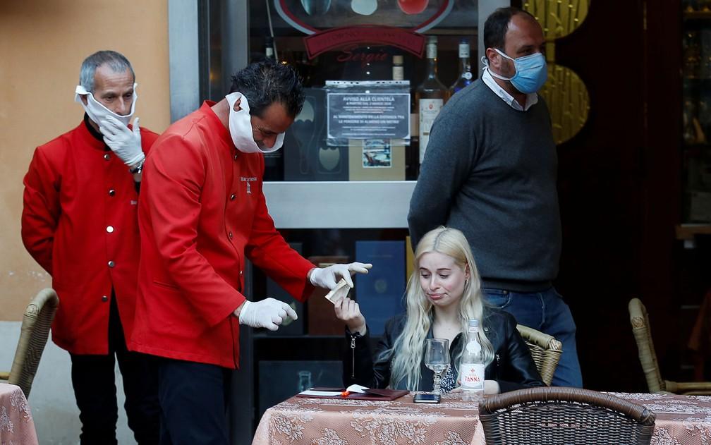Garçom com luvas recebe pagamento de cliente em restaurante em Roma, na Itália, na quarta-feira (11) — Foto: Reuters/Remo Casilli