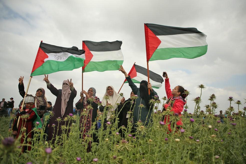 Mulheres palestinas acenam com bandeiras palestinas e mostram o gesto de vitória durante um protesto perto da fronteira com Israel, na Faixa de Gaza, em 30 de março de 2018. (Foto: Mohammed Abed/AFP)