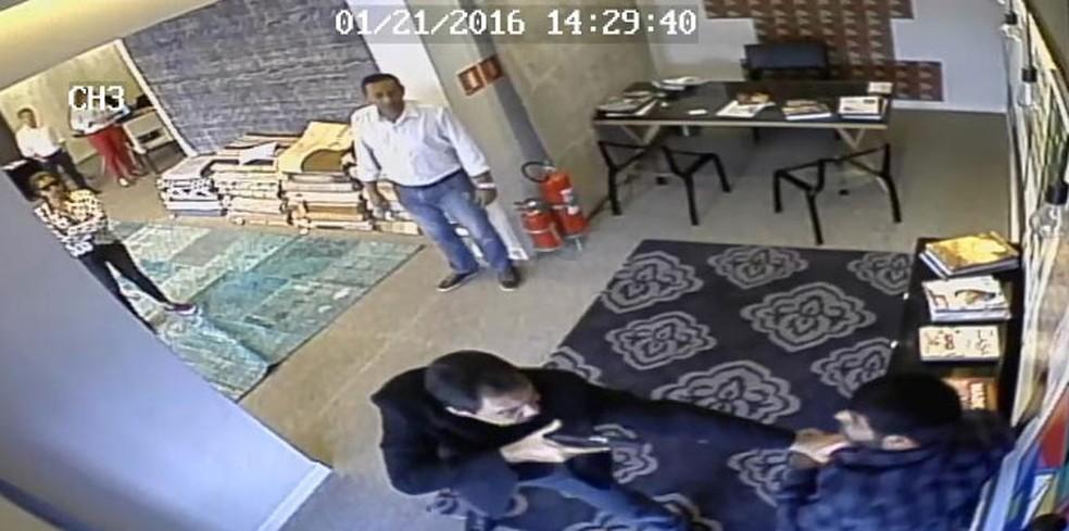 José Camilo Leonel aponta arma para comerciante iraniano; ao fundo, Iolanda Santos observa de braços cruzados — Foto: Reprodução/Câmera de Segurança