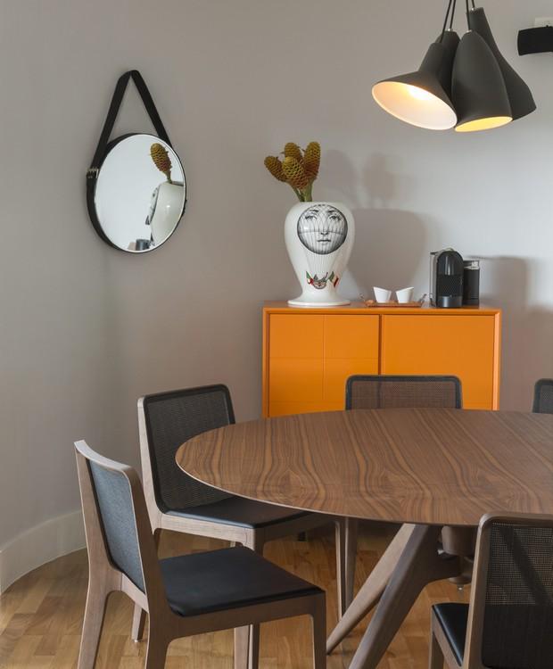 A curva estrutural da casa aparece atrás do bar Mondrian, da Clami, e ganha força com a mesa redonda e as cadeiras de Jader Almeida. Pendentes Fulano, Ciclano e Beltrano, da La Lampe, vaso Fornasetti e espelho da Marché Art de Vie. (Foto: Evelyn Muller)