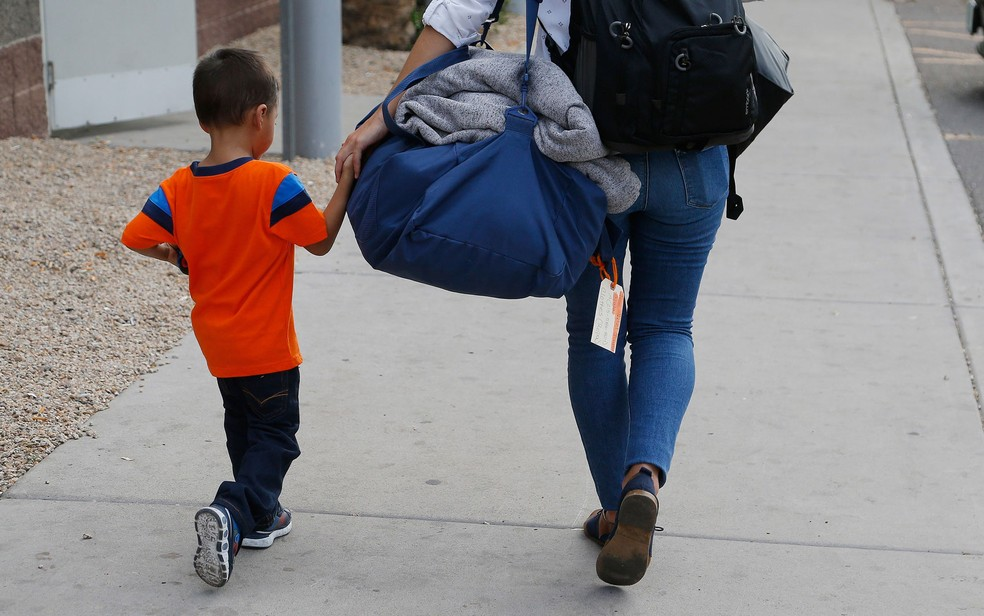 O hondurenho José Jr, de 3 anos, é levado até seu pai, a quem foi entregue na terça-feira (10), em Phoenix (Foto: AP Photo/Ross D. Franklin)
