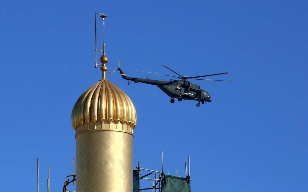Helicóptero militar iraquiano sobrevoa o santuário Imam Ali em Najaf, durante a visita do Papa Francisco à cidade sagrada para encontro histórico com o clérigo xiita grande Aiatolá Ali al-Sistani — Foto: Mohammed Sawaf / AFP Photo