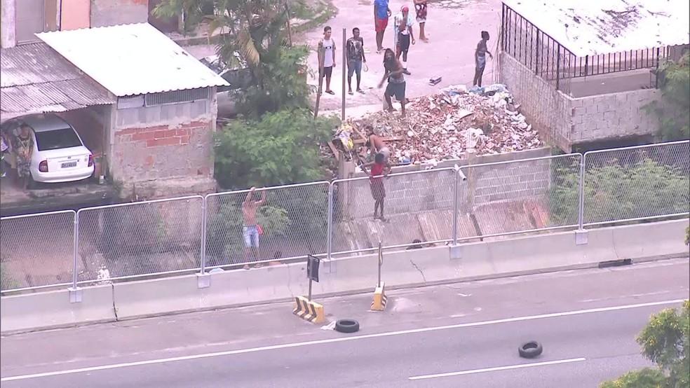 Homens atiram pneus na Linha Amarela, para impedir a passagem dos motoristas (Foto: Reprodução/ TV Globo)