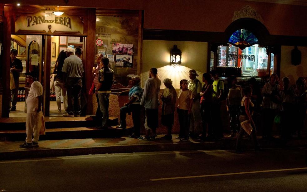 Moradores de El Hatillo, nas proximidades de Caracas, fizeram fila no último sábado (23) em uma padaria para comprar pão em dia de corte de energia — Foto: Foto AP/Fernando Llano
