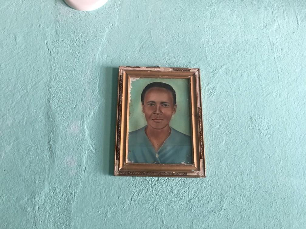 Quadro de Maria São Pedro jovem fica pendurado na parede da sala da casa dela — Foto: João Souza/G1