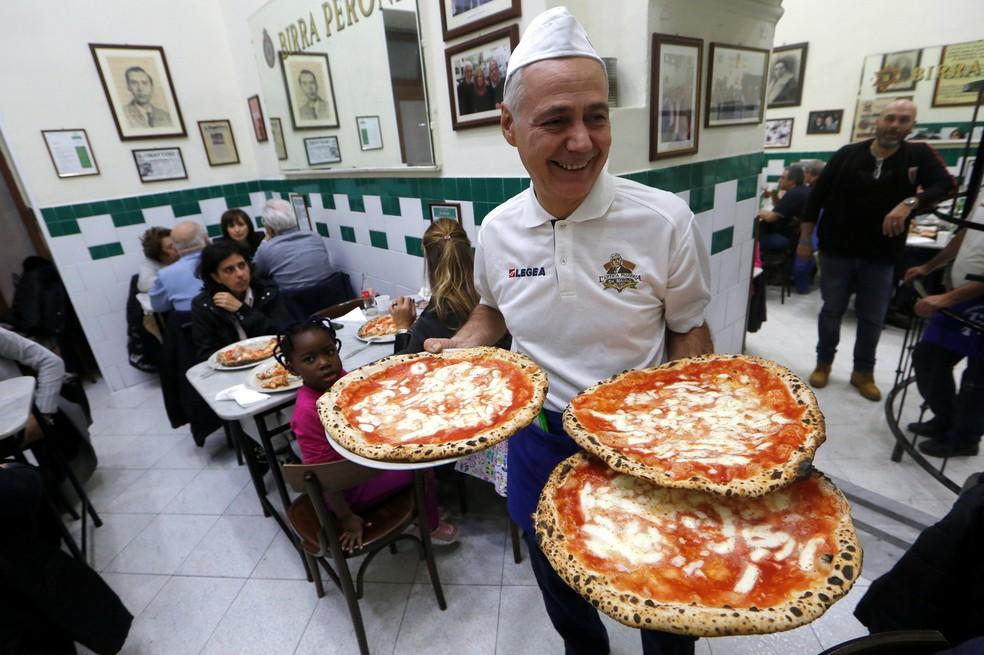 -  Garçom serve pizzas na L Antica Pizzeria da Michele, em Nápoles  Foto: Ciro De Luca/Reuters