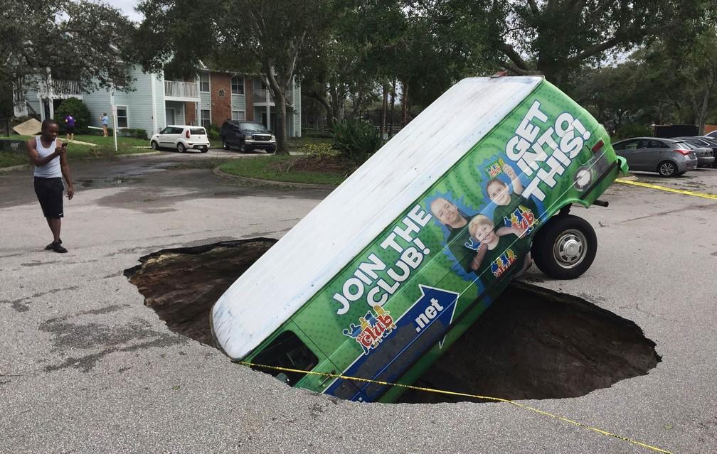 Jovem fotografa um furgão que caiu dentro de uma cratera formada no meio de uma rua de Winter Springs, na Flórida, após a passagem do furacão Irma (Foto: Joe Burbank/Orlando Sentinel via AP)