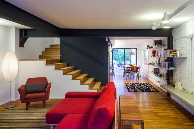 Após reforma, o piso térreo da casa foi quase totalmente integrado. Os tijolos da parede foram expostos e pintados de branco para realçar a decoração. (Foto: Pedro Vannucchi)