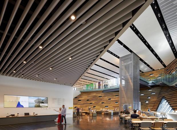 No térreo, uma cafeteria é cercada por paredes de madeira inclinadas (Foto: Hufton + Crow/ Reprodução)